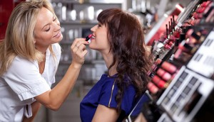 Make up artist applying lipstick to a customer in a beauty store. Selective focus.