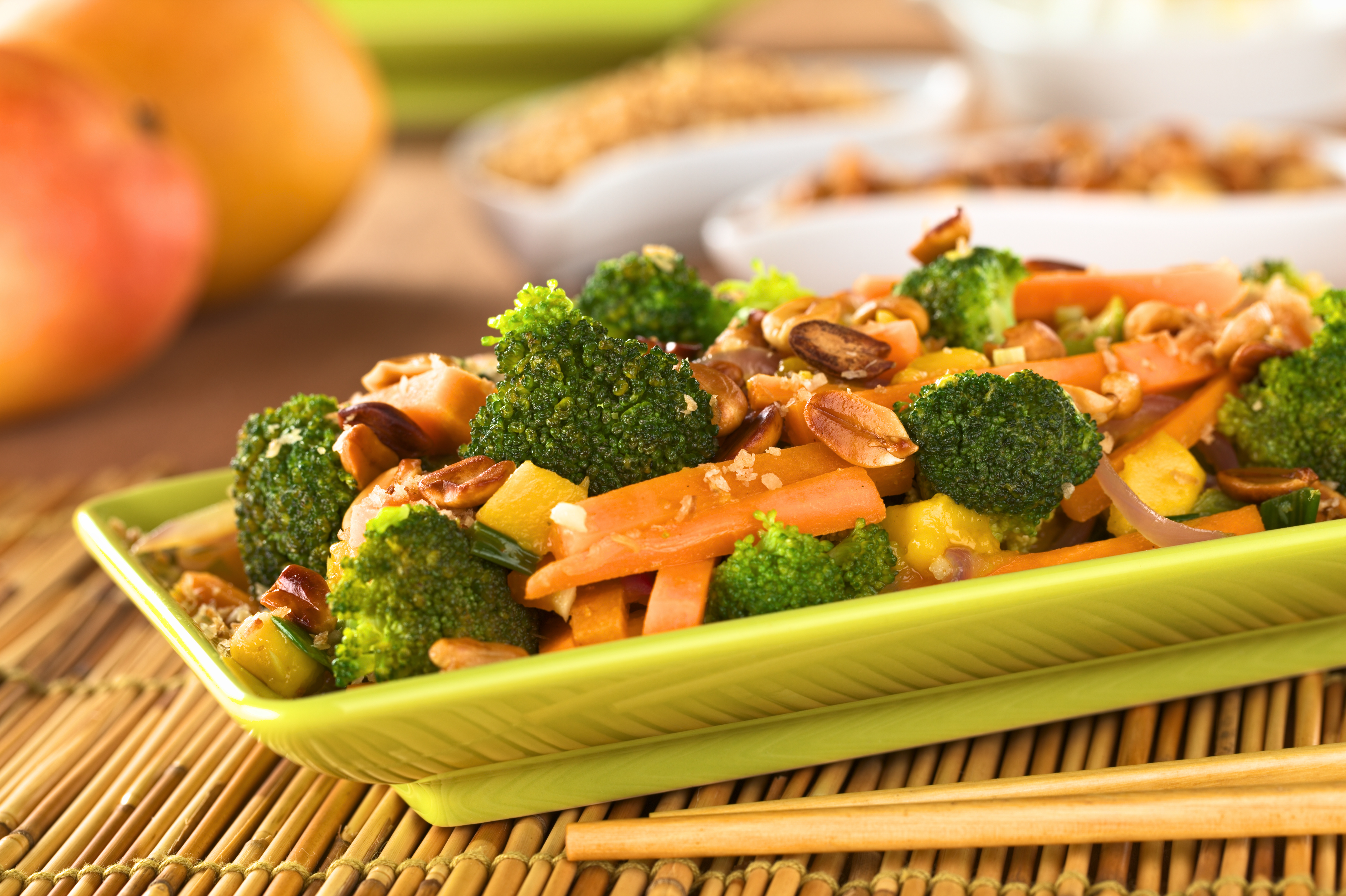 Vegetarian stir-fry Thai-style with broccoli, carrot, onion, mango with fried coconut flakes and peanuts (Selective Focus, Focus on the broccoli in the middle of the image)
