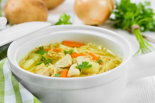 Soup with noodles and chicken in a white ceramic bowl