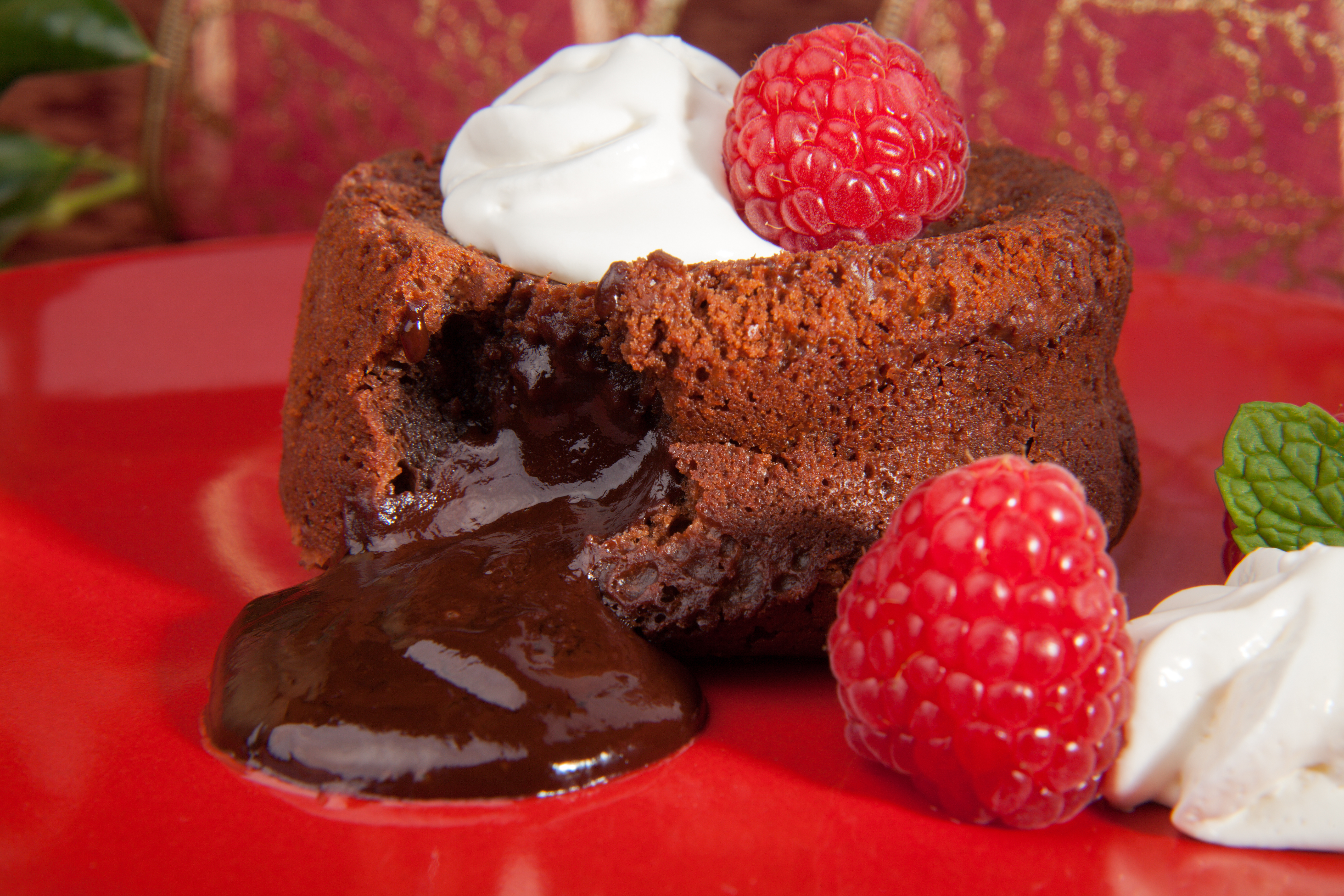Delicious dark chocolate lava cake dessert served with whipped cream and fresh raspberries. Surrounded by Christmas ornaments.